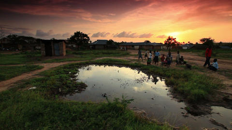 Boys playing at village water hole at sunset in Africa Footage