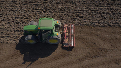 Aerial - Tractor smoothing out a tilled field with a harrow Footage