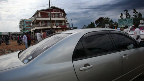 Tracking footage of Kenyan town road filled with people, vehicles Footage