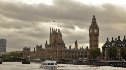 Dark storm clouds behind Big Ben and Westminster palace, Thames river, flying bi Footage