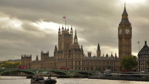 Boat glides across Thames river in front of Westminster palace in London, Englan Footage