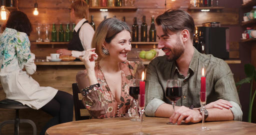 A young man and a woman flirting and enjoying red wine Footage