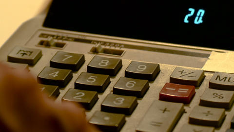 hands detail on ancient led calculator, footage to represent business and Live Action