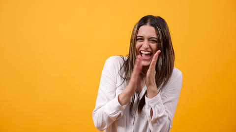 Happy excited woman clapping on yellow background Footage