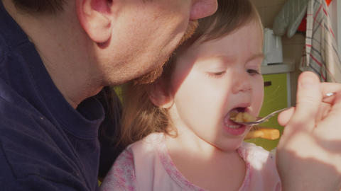 Father feeding fidgeting small daughter by spoon at kitchen Footage