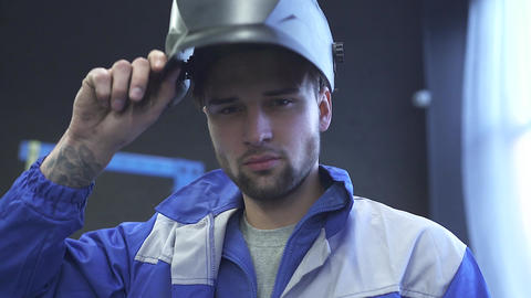 Portrait handsome specialist auto mechanic in welding helmet on the background Live Action