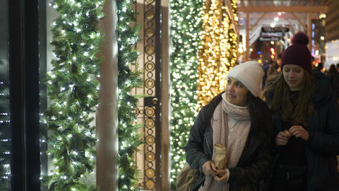 Two girls in New York look at Christmas decorated shop windows Footage