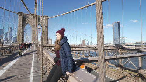 Young beautiful woman relaxes on Brooklyn Bridge while enjoying the amazing view Footage