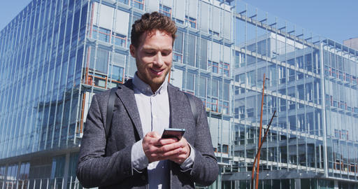 Man sms texting using app on smart phone in city - business man on smartphone Live Action