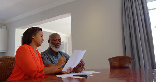 Front view of mature black couple discussing domestic bills in a comfortable home 4k Live Action