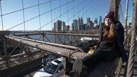 Young and reckless girl sits on the rim of Brooklyn Bridge New York Footage
