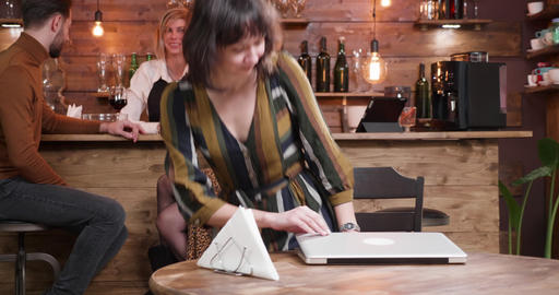 Pretty woman starts working on her laptop in a busy cafe GIF