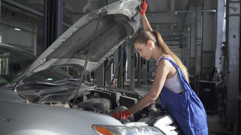 Female young auto specialist opening the hood of the car for repairing or making Live Action