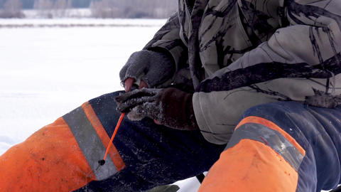 Fisherman catches a fish under ice. Ice fishing Archivo