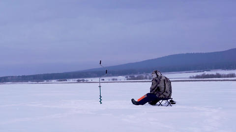 Fisherman catches a fish under ice. Ice fishing Live Action