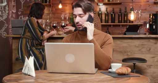 A handsome young businessman talking on his phone while working in a bar Footage