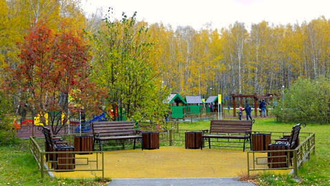 fenced recreation area against children playground in park Live Action