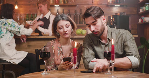 A young numb couple distracted by social media while on a date Footage