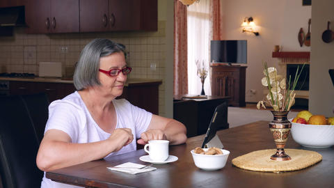 Senior woman with coffee using digital tablet pc at home GIF