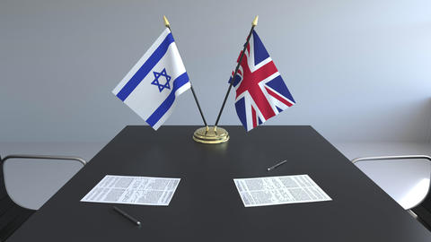 Flags of Israel and Great Britain and papers on the table. Negotiations and Footage