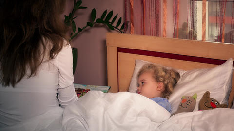 toddler girl child in bed with toy cats and listening to mother reading book Footage