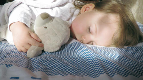 Cute little girl with blond hair sleeping on the bed and lit by the sun with a Footage