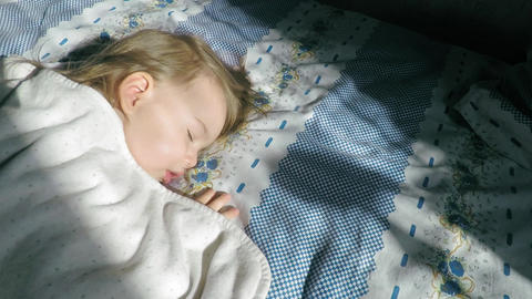 A little girl with blond hair is sleeping on the bed and lit by sunlight Footage