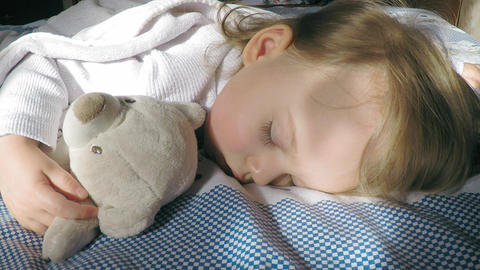 Beautiful little girl with blond hair sleeping on the bed and lit by the sun Footage