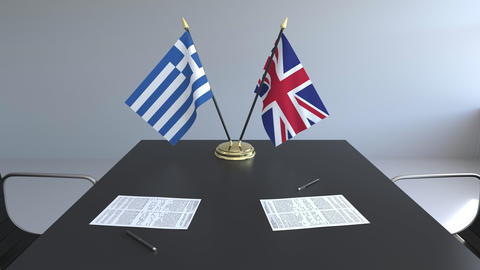 Flags of Greece and Great Britain and papers on the table. Negotiations and Live Action