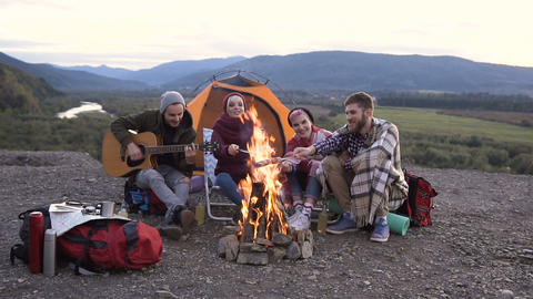 Young guy traveler is playing the guitar, his friends are cooking sausages on Footage