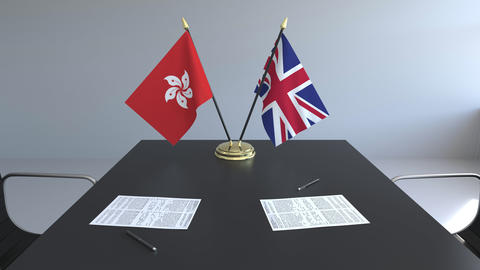 Flags of Hong Kong and Great Britain and papers on the table. Negotiations and Live Action
