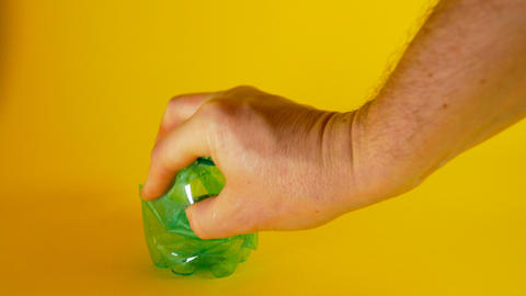 A man's hand crushes a green disposable plastic bottle on a yellow background Live Action