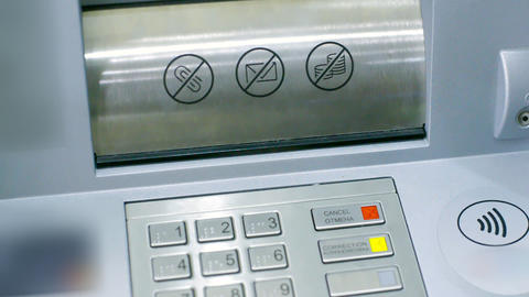 closeup ATM slot cover opens woman puts banknote backwards GIF