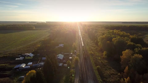 aerial picture freight train moves to horizon at sunset Footage