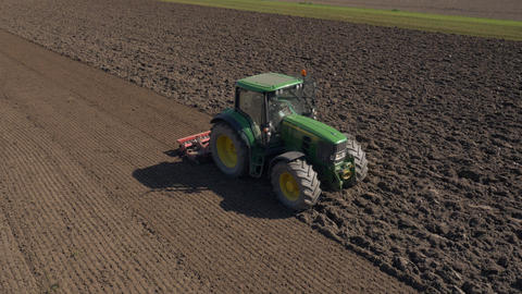 Aerial - Farm machinery with a rolling harrow smoothing out the soil Live Action