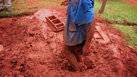 KENYA-C.2012 A man mixes red clay with his feet in Kenya, Africa c.2012 Live Action