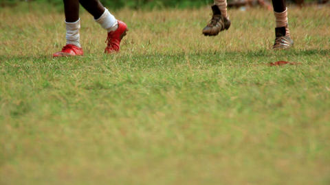 Three pairs of feet wearing cleats walk by Footage