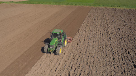 Aerial - Agricultural machinery with harrows smoothing out the seed bed Footage
