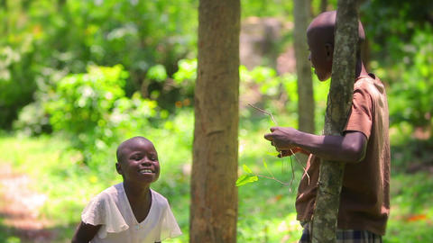 Two little african kids playing, laughing and jamming out in front of the camera Footage