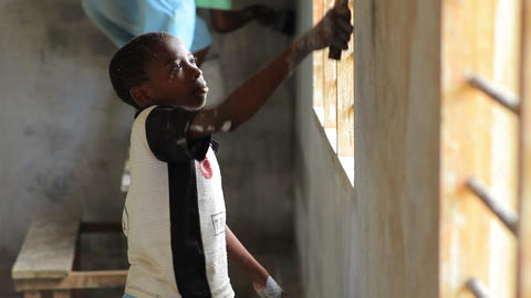 Child painting the inside of a building in Kenya Footage