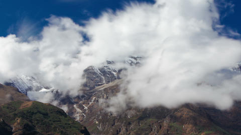 Panning shot of Time-lapse of clouds moving around Himalayan mountains Footage