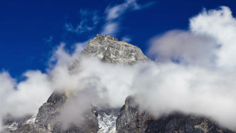 Panning shot of Time-lapse of clouds swirling around a Himalayan peak Footage