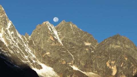 Panning shot of Time-lapse of the moon going behind Himalayan peaks in the morni Footage