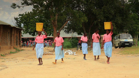 Girls carrying buckets of water on their heads in Kenya Footage