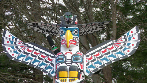 Close up of colorful bird figure atop First Nation totem pole Footage