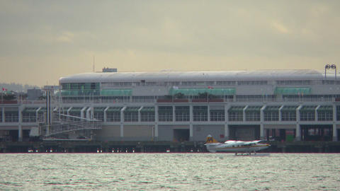 Water plane taxis in Vancouver harbor in front of large building Footage