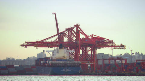 Long shot of huge cranes loading cargo on an ocean barge Footage