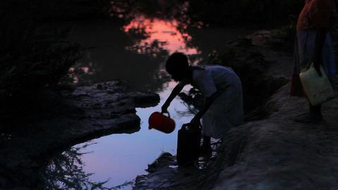 Girl filling a water bucket near a village in Kenya Footage