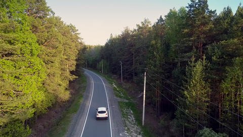 upper auto drives along road and power lines in pine wood Footage