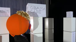 Big Orange Head President Punching Obamacare Box Live Action